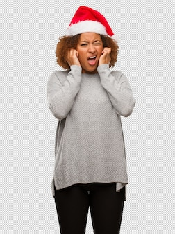 Young black woman wearing a santa hat covering ears with hands