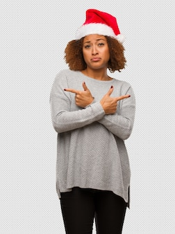 Young black woman wearing a santa hat decide between two options
