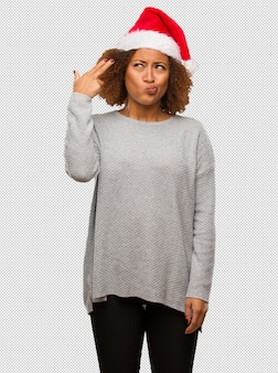 Young black woman wearing a santa hat doing a suicide gesture