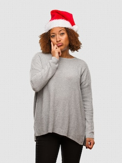 Young black woman wearing a santa hat doubting and confused