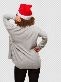 Young black woman wearing a santa hat from behind thinking about something