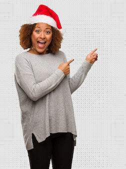 Young black woman wearing a santa hat holding something with hand