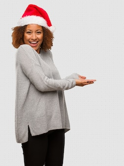 Young black woman wearing a santa hat holding something with hands
