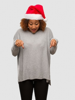 Young black woman wearing a santa hat pointing down