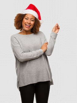 Young black woman wearing a santa hat pointing to the side with finger
