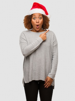Young black woman wearing a santa hat pointing to the side