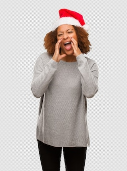 Young black woman wearing a santa hat shouting something happy to the front