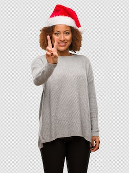 Young black woman wearing a santa hat showing number two