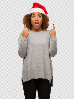 Young black woman wearing a santa hat surprised pointing up to show something