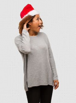 Young black woman wearing a santa hat try to listening a gossip