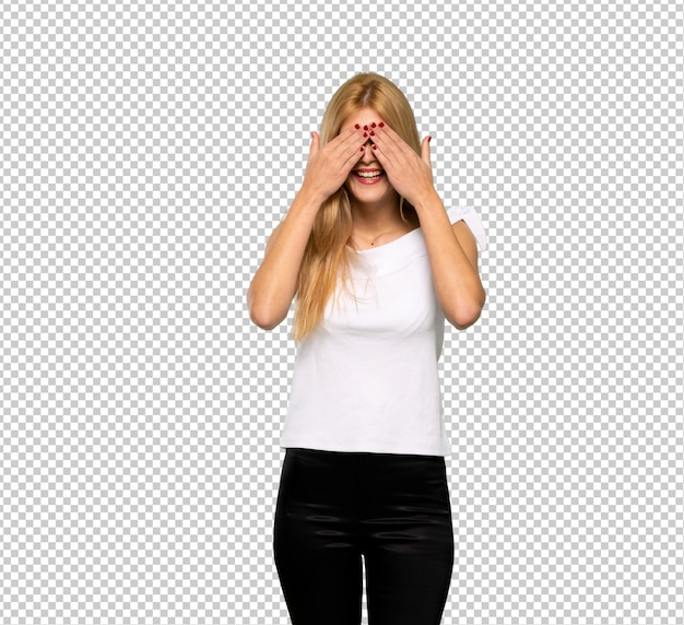 Young blonde woman covering eyes by hands. surprised to see what is ahead