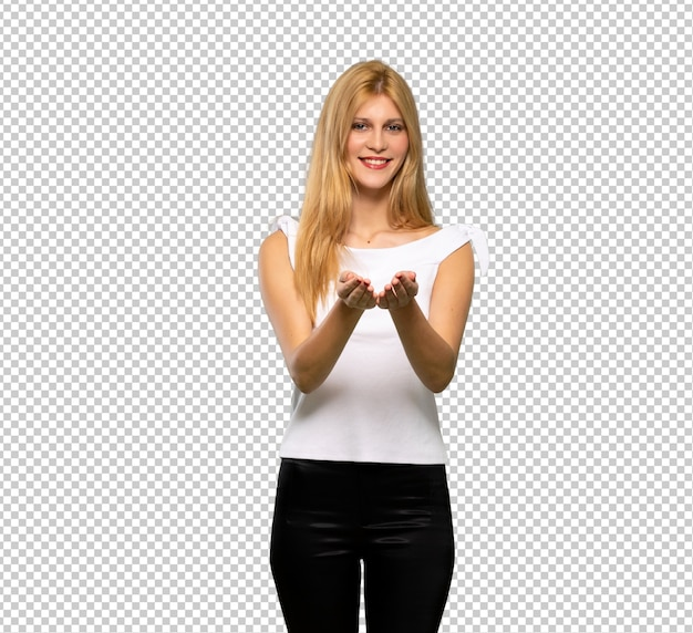 Young blonde woman holding copyspace imaginary on the palm to insert an ad