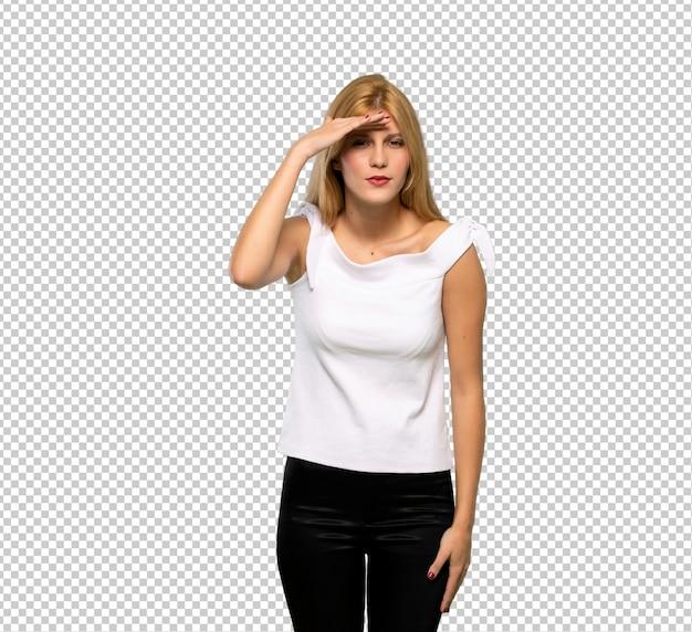 Молодая блондинка, глядя далеко с рукой, чтобы посмотреть что-то