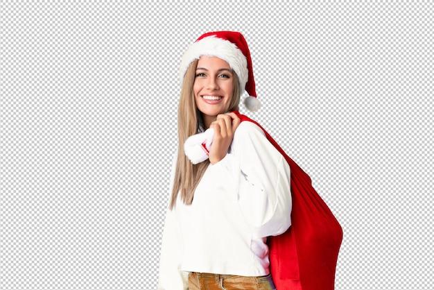 Молодая блондинка поднимает сумку, полную подарков