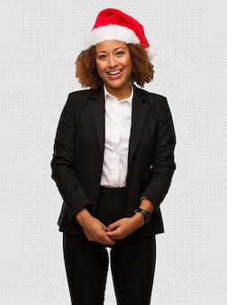 Young business black woman wearing a chirstmas santa hat cheerful with a big smile