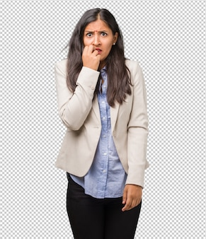 Young business indian woman biting nails, nervous and very anxious and scared for the futu