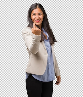 Young business indian woman inviting to come, confident and smiling making a gesture with