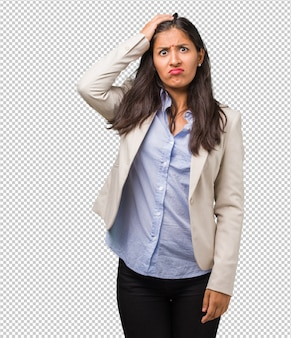 Young business indian woman worried and overwhelmed, forgetful, realize something