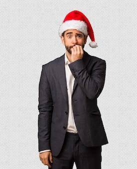 爪、緊張し、非常に不安をかむサンタの帽子を身に着けている若いビジネスマン