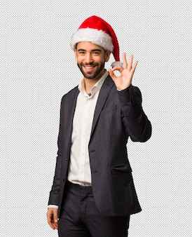 Young business man wearing santa hat cheerful and confident doing ok gesture