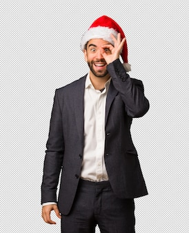Young business man wearing santa hat confident doing ok gesture on eye