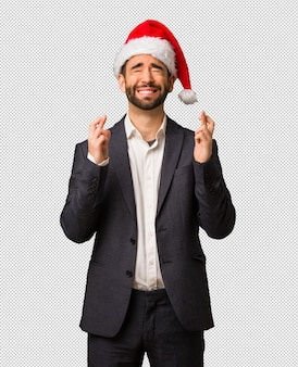 Young business man wearing santa hat crossing fingers for having luck