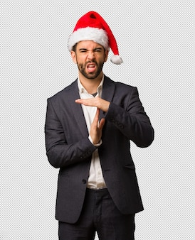 Young business man wearing santa hat doing a timeout gesture