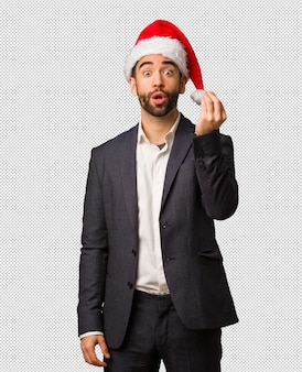 Young business man wearing santa hat doing a typical italian gesture