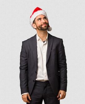 Молодой деловой человек в шляпе санта мечтает достичь целей и задач