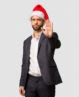 Young business man wearing santa hat putting hand in front