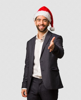 Young business man wearing santa hat reaching out to greet someone
