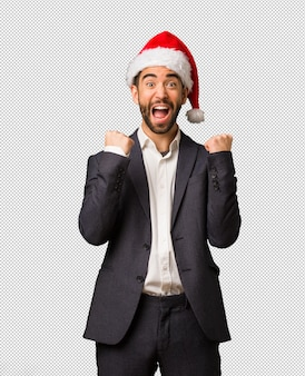 サンタの帽子を着た若いビジネスマンは驚いて、ショックを受けました