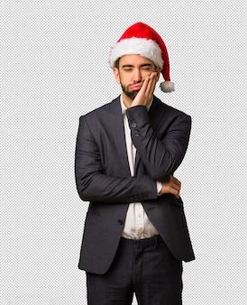 疲れて、非常に眠く、サンタの帽子を身に着けている若いビジネスマン