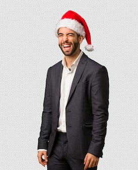 Young business man wearing santa hat winking, funny, friendly and carefree gesture