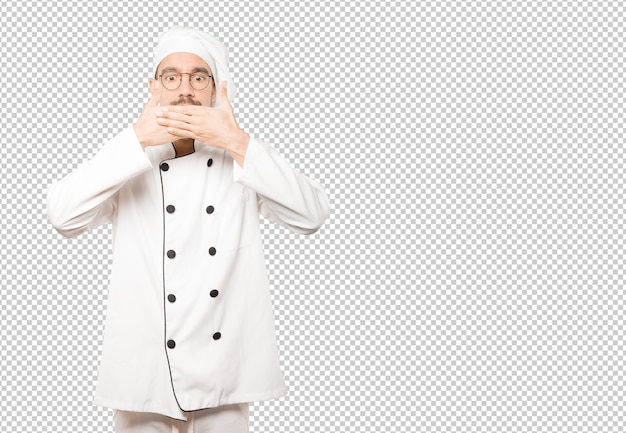 Young chef covering his mouth with his hands