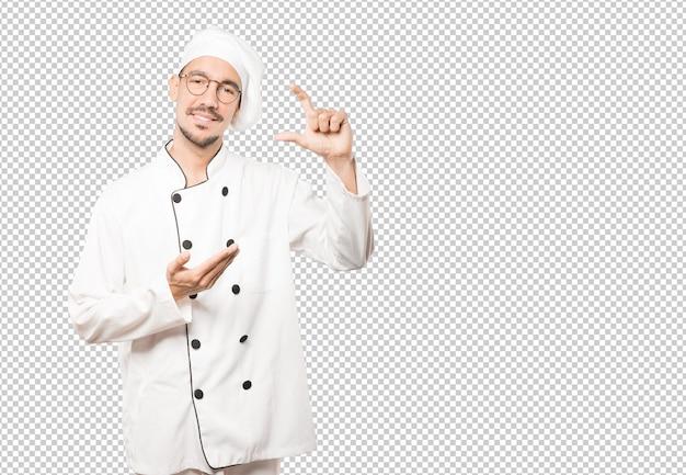 Молодой шеф-повар делает жест маленького размера рукой