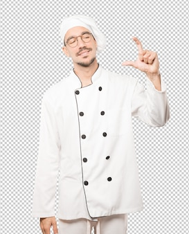 Young chef doing a gesture of small size with his hand