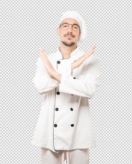 Молодой шеф-повар делает жест, не скрестив руки