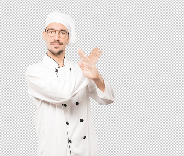 Young chef making a gesture of not crossing with the arms