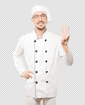 Young chef making a number three gesture