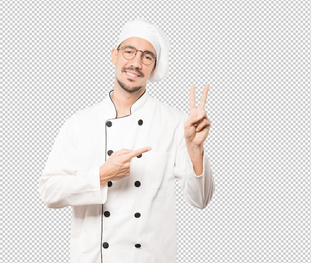 Young chef making a number two gesture