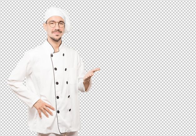 Young chef waving with his hand