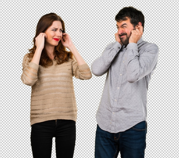 Young couple covering their ears