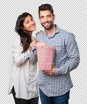 ポップコーンを保持している若いカップル
