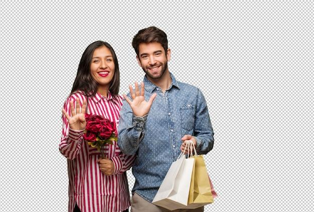 Молодая пара в день святого валентина показывает номер девять