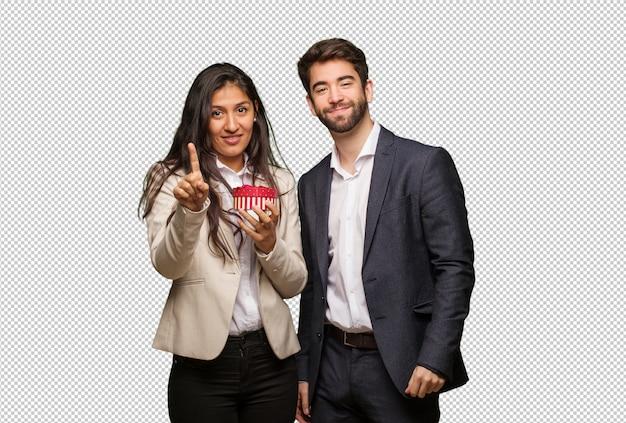 Молодая пара в день святого валентина, показывая номер один