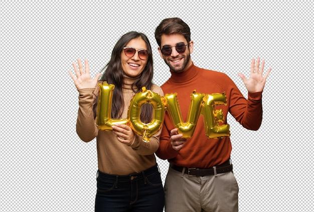 Молодая пара в день святого валентина показывает номер десять