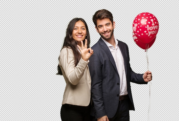 Молодая пара в день святого валентина показывает номер три