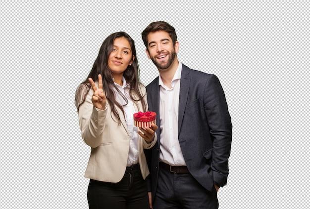 Молодая пара в день святого валентина показывает номер два