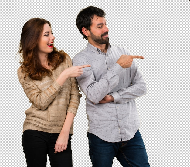 Young couple pointing to the lateral